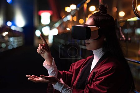attractive asian girl using virtual reality headset and pointing on something on street in evening, city of future concept