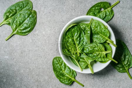 Top view of wet spinach leaves in bowl