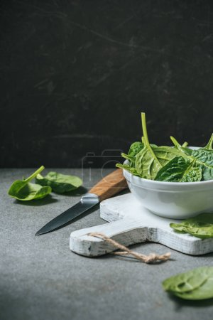 Organic fresh spinach leaves in white bowl on cutting board near metal knife