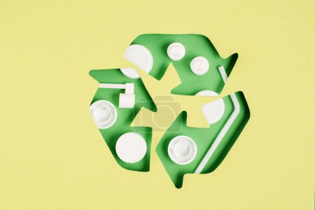 Top view of green recycle sign with bottle caps pattern on yellow background