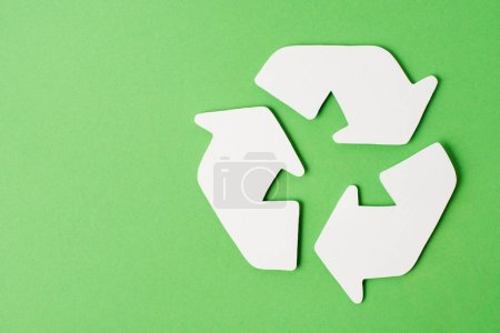 Top view of white recycle sign on green background