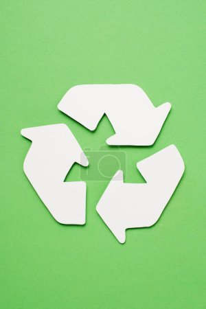 Top view of white trash recycle sign with arrows on green background