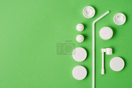 Top view of different plastic bottle caps and drinking straw on green background