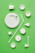 Top view of plastic bottle caps, drinking straw and lid for drink on green background