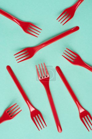 Top view of red plastic forks scattered on blue background