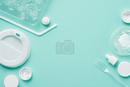 Photo for Top view of plastic bottle caps, drinking straw, fork, eggs tray and lid for drink on blue background - Royalty Free Image