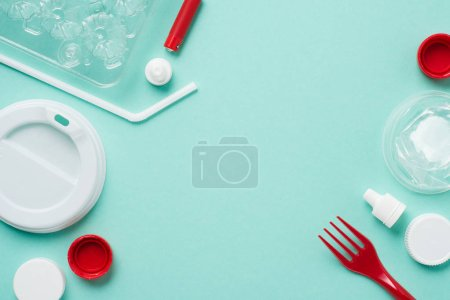 Photo for Top view of plastic bottle caps, drinking straw, fork, eggs tray and lid on blue background - Royalty Free Image