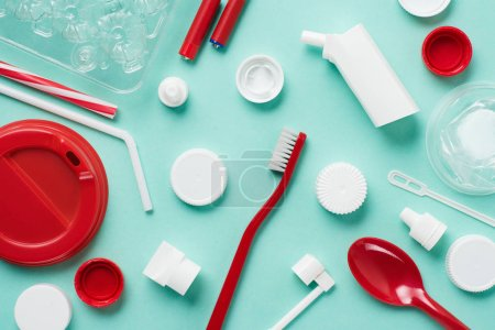 Top view of different kinds of disposable plastic garbage on blue background