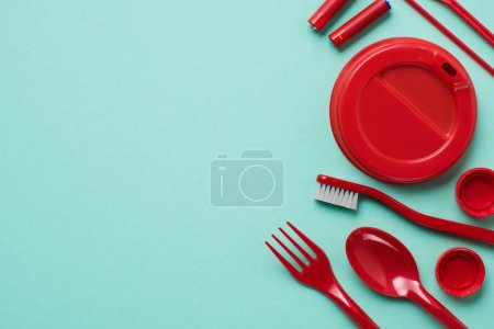 Top view of red plastic bottle caps, fork, spoon, lid for drink, batteries and toothbrush on blue background