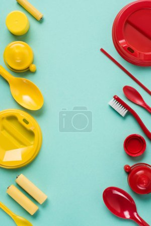 Flat lay with red and yellow disposable plastic wares arranged on blue background