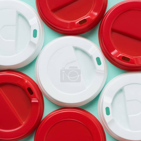 Close up view of red and white lids for drink on blue backgroun