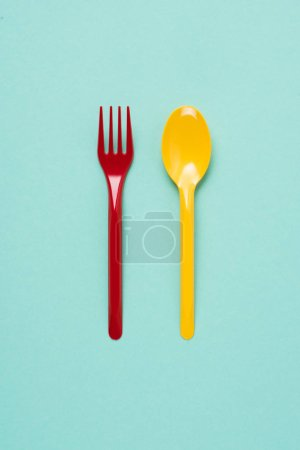 Photo for Top view of red plastic fork and yellow spoon on blue background - Royalty Free Image