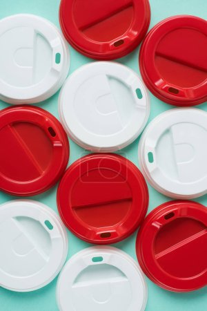 Top view of red and white disposable lids for drink arranged on blue background