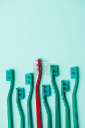 Top view of plastic colorful toothbrushes arranged on blue background