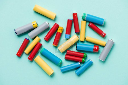 Top view of colorful batteries scattered on blue background