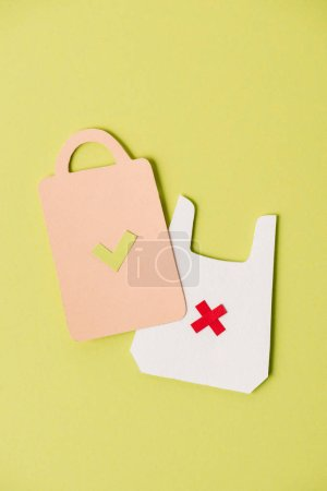 Paper models of bag and packet on yellow background