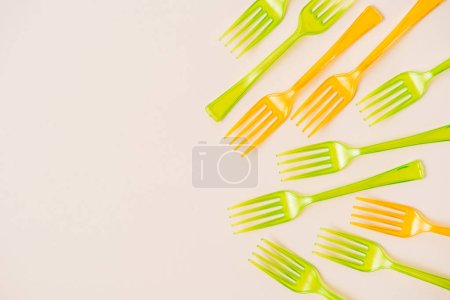 Top view of colorful plastic forks on pink background
