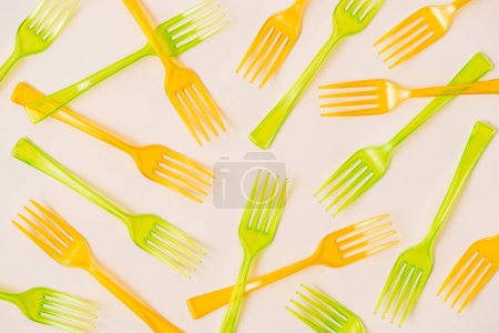 Top view of orange and green plastic forks on pink background