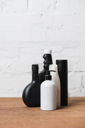 Black and white plastic bottles on wooden table on brick wall background