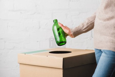 Partial view of woman throwing glass bottle in trash bin