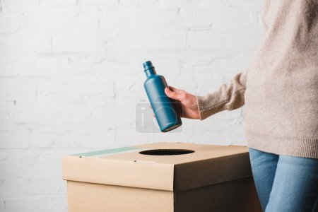 Cropped view of woman throwing plastic bottle in trash bin