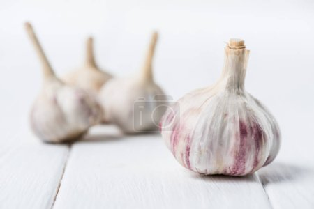 Photo for Ripe garlic bulbs on white wooden table - Royalty Free Image