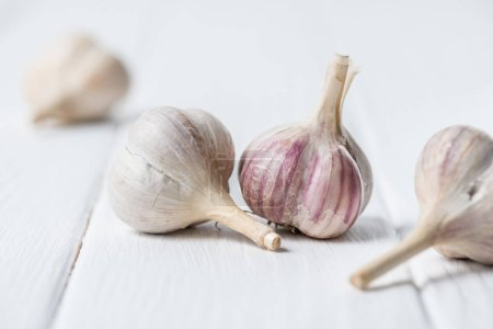 Photo for Ripe garlic heads on white wooden table - Royalty Free Image