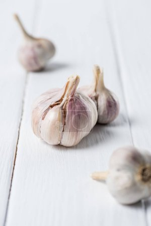 Photo for Several garlic bulbs on white wooden table - Royalty Free Image