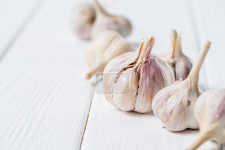 Photo for Several ripe garlic bulbs on white rustic table - Royalty Free Image