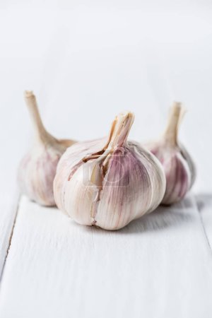 Photo for Ripe garlic heads on white rustic table - Royalty Free Image