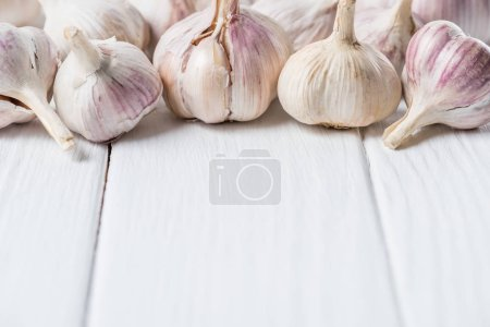 Photo for Ripe garlic heads on white rustic cook table - Royalty Free Image