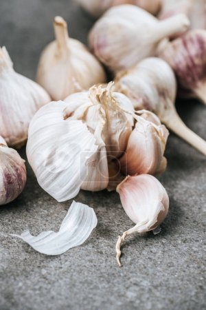 Photo for Garlic bulbs and peeled cloves on grey textured surface - Royalty Free Image