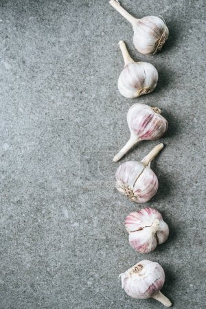 top view of vertical row of ripe garlic bulbs on grey background