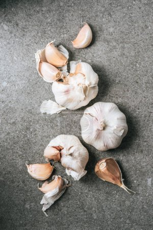 Photo for Top view of ripe bulbs and cloves of garlic on grey stone table - Royalty Free Image
