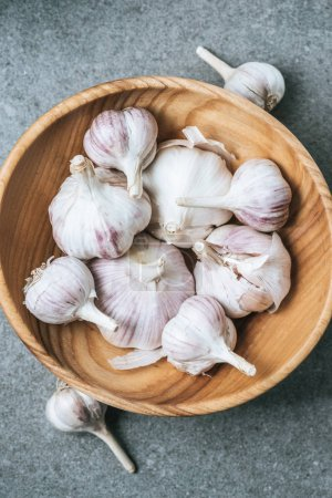 top view of ripe garlic bulbs in wooden bowl on grey textured background