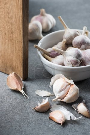 Photo for Garlic in ceramic bowl, several peeled cloves and wooden chopping board on grey background - Royalty Free Image