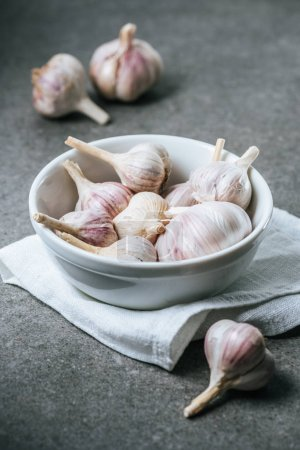 Photo for Garlic bulbs in ceramic bowl with white cloth on grey background - Royalty Free Image