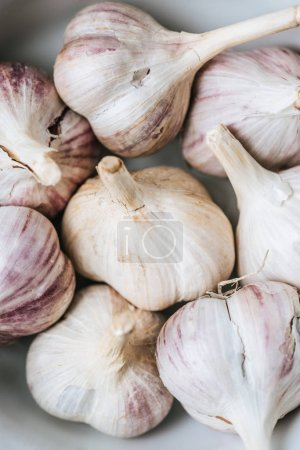 Photo for Close up of ripe garlic heads in white ceramic bowl - Royalty Free Image