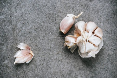 top view of peeled ripe garlic bulb and several cloves on grey background