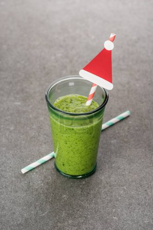 Homemade green organic smoothie in glass with straws and christmas decoration