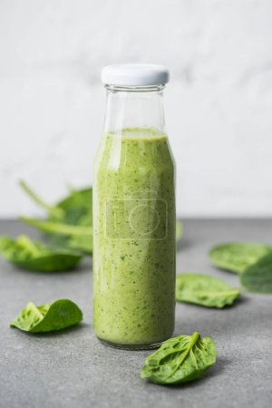 Green blended organic smoothie in glass bottle