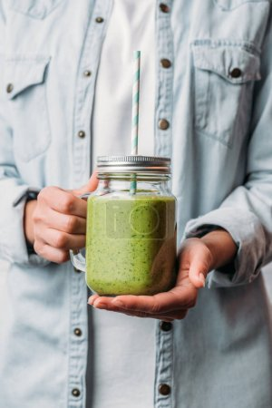 Female hands holding glass jar with green nutritious smoothie and straw