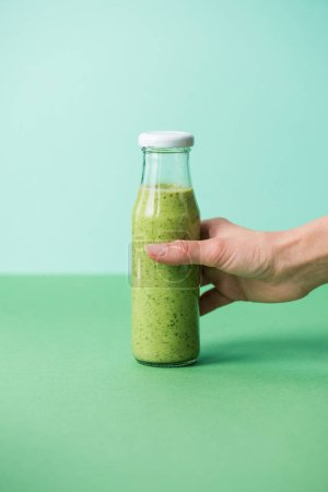Female hand holding glass bottle with fresh organic smoothie