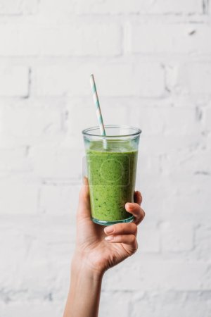 Photo for Female hand holding glass with green organic smoothie and straw - Royalty Free Image