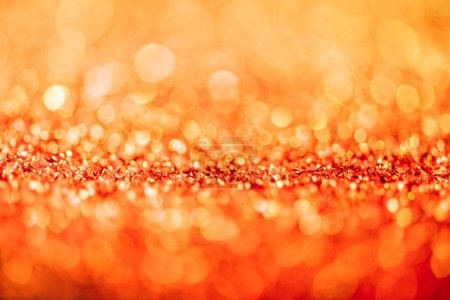 abstract christmas background with orange glitter and bokeh