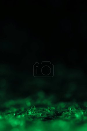 green glitter on black background with copy space