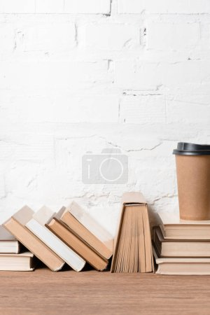 books and disposable coffee cup on wooden table