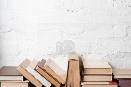 Photo pour Livres avec couvertures rigides près du mur de briques blanches, fond éducatif - image libre de droit