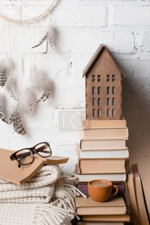 books, cup of coffee, eyeglasses, blanket and dream catcher near white brick wall