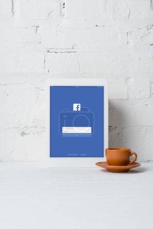 Foto de Tableta digital con aplicación de facebook y taza de café junto a la pared de ladrillo blanco - Imagen libre de derechos